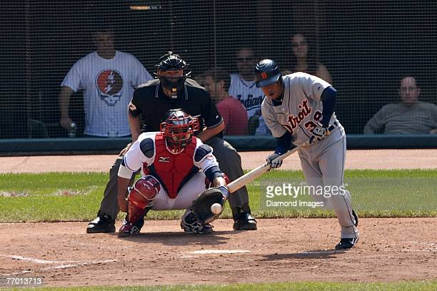 Infielder Ramon Santiago#39 of the Detroit Tigers bunts as catcher Victor Martinez of the Cleveland Indians and homeplate umpire Gary Darling look on...