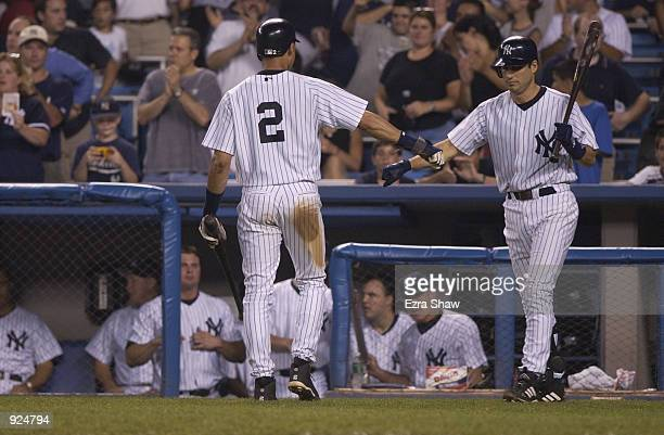 Infielder Robin Ventura of the New York Yankees congratulates teammate Derek Jeter against the Cleveland Indians during the game on July 2 2002 at...