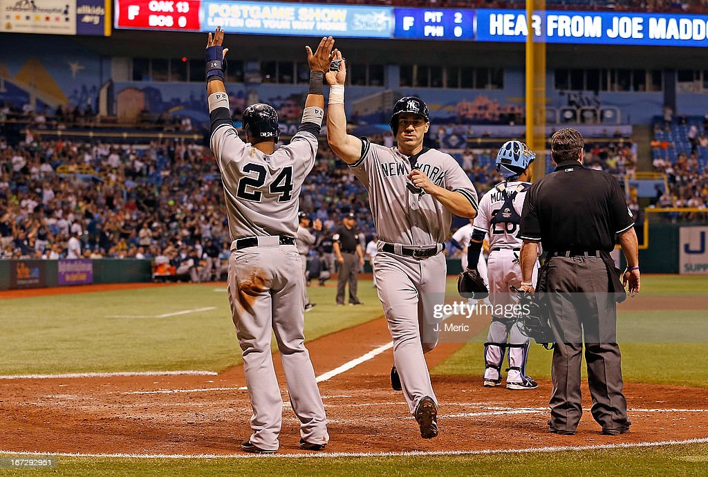 Infielder Robinson Cano #24 of the New York Yankees congratulates Travis Hafner #33 as he scores the winning run in the ninth inning against the Tampa Bay Rays at Tropicana Field on April 23, 2013 in St. Petersburg, Florida.