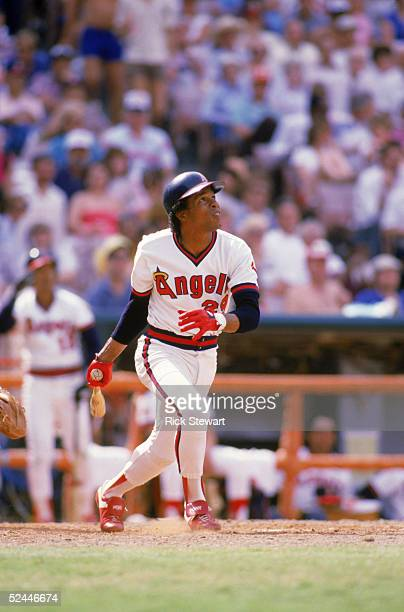 Infielder Rod Carew of the California Angels watches the flight of his hit as he runs to first during a 1985 MLB game at Angel Stadium in Anaheim...
