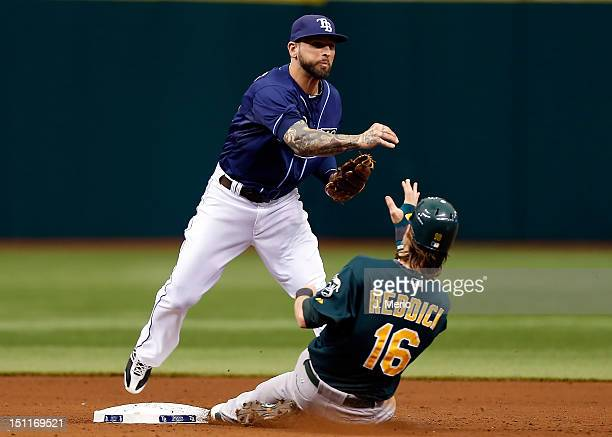 Infielder Ryan Roberts of the Tampa Bay Rays turns a double play as Josh Reddick of the Oakland Athletics tries to break it up during the game at...