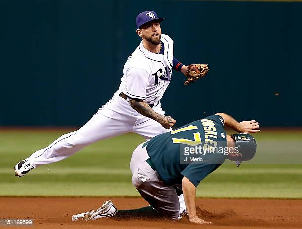 Infielder Ryan Roberts of the Tampa Bay Rays turns a double play as Adam Rosales of the Oakland Athletics tries to break it up during the game at...