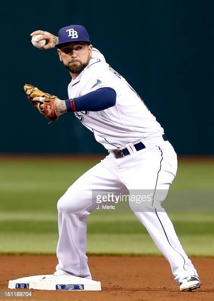 Infielder Ryan Roberts of the Tampa Bay Rays turns a double play against the Oakland Athletics during the game at Tropicana Field on August 24 2012...