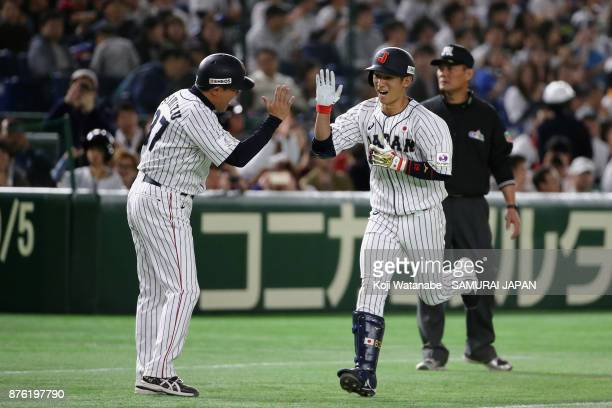 Infielder Ryoma Nishikawa of Japan celebrates with Coach Masaji Shimizu after hitting a solo homer in the bottom of seventh inning during the Eneos...