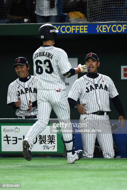 Infielder Ryoma Nishikawa of Japan is congratulated by Head coach Atsunori Inaba after hitting a solo homer in the bottom of seventh inning during...