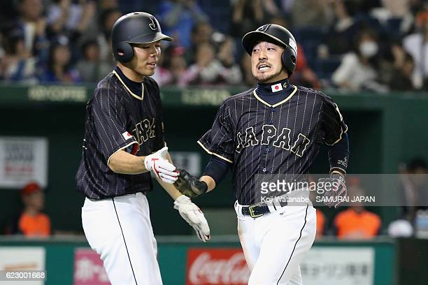 Infielder Ryosuke Kikuchi and Outfielder Shogo Akiyama of Japan celebrate their run by Infielder Tetsuto Yamada of Japan in the seventh inning during...