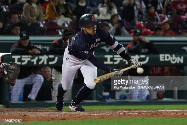 Infielder Ryosuke Kikuchi of Japan lays down for a squeeze bunt to make it 4-3 in the top of 9th inning during the game four between Japan and MLB...