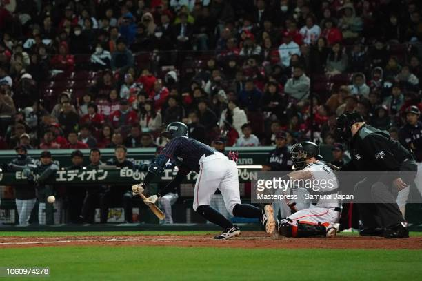 Infielder Ryosuke Kikuchi of Japan lays down for a squeeze bunt to make it 43 in the top of 9th inning during the game four between Japan and MLB All...