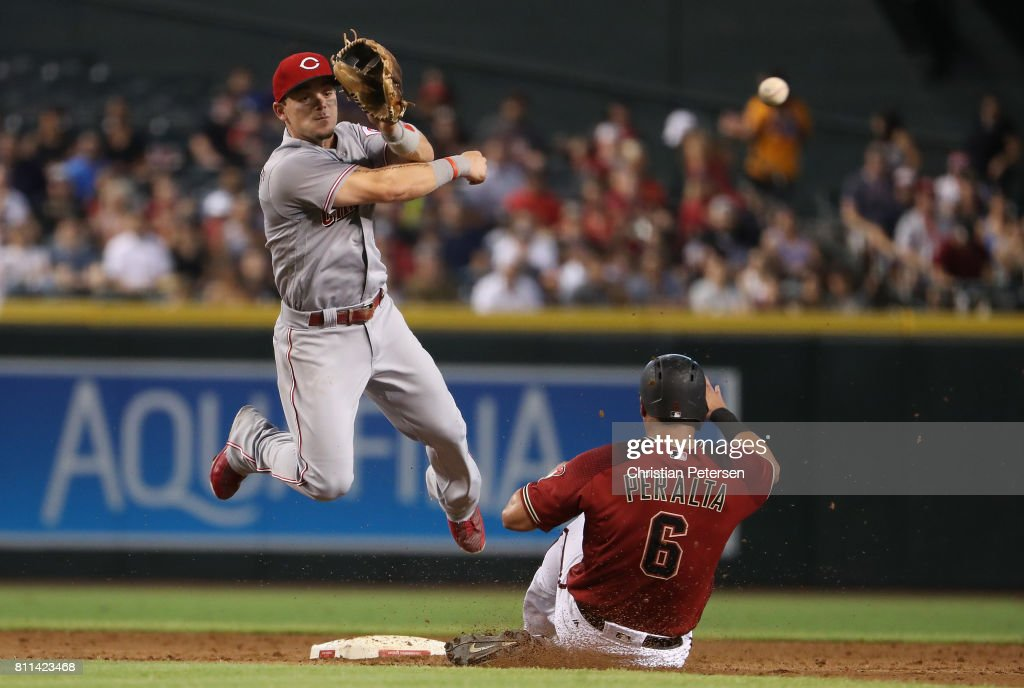 Infielder Scooter Gennett #4 of the Cincinnati Reds throws over the sliding David Peralta #6 of the Arizona Diamondbacks to compete a double play during the third inning of the MLB game at Chase Field on July 9, 2017 in Phoenix, Arizona.