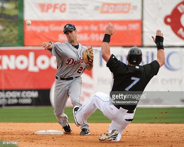 Infielder Scott Sizemore of the Detroit Tigers starts a double play over sliding outfielder Jeremy Reed of the Toronto Blue Jays March 22 2010 at...
