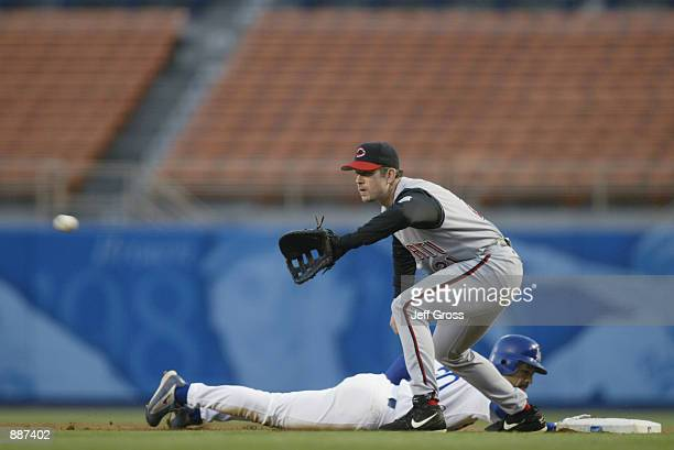 Infielder Sean Casey of the Cincinnati Reds waits for the throw as outfielder Dave Roberts of the Los Angeles Dodgers slides back to the base during...