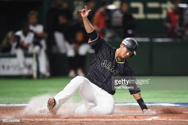 Infielder Sho Nakata of Japan slides safely into the home plate to make it 10 after a sacrifice fly by Outfielder Shogo Akiyama of Japan in the top...