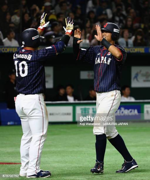 Infielder Shogo Nakamura of Japan celebrates with designated hitter Kensuke Kondo after scoring a run to make it 50 in the top of seventh inning...