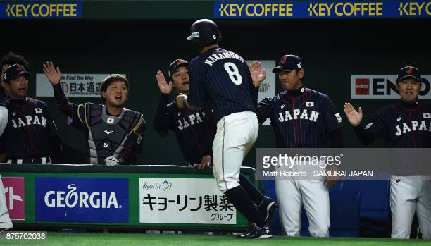 Infielder Shogo Nakamura of Japan high fives with Head coach Atsunori Inaba and team mates after scoring a run to make it 50 in the top of seventh...