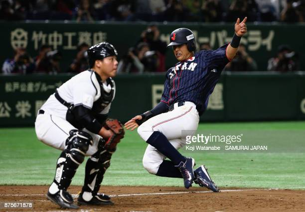 Infielder Shogo Nakamura of Japan slides safely into the home plate to score a run to make it 31 by the tworun single by Infielder Yota Kyoda in the...