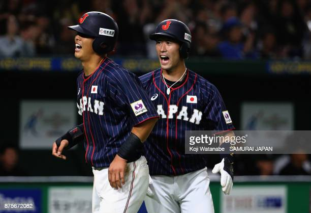 Infielder Shuta Tonosaki and Infielder Shogo Nakamura of Japan celebrate after scoring runs by a single of Infielder Yota Kyoda to make it 31 in the...
