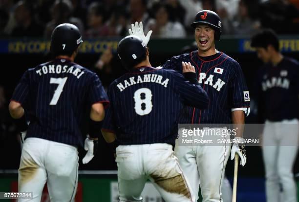 Infielder Shuta Tonosaki and Infielder Shogo Nakamura of Japan celebrate with Infielder Go Matsumoto after scoring runs by a single of Infielder Yota...
