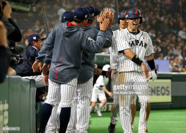 Infielder Shuta Tonosaki of Japan high fives with team mates after scoring a run in the bottom of fifth inning during the Eneos Asia Professional...