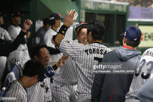 Infielder Shuta Tonosaki of Japan is congratulated by team mates in the dugout in the bottom of fifth inning during the Eneos Asia Professional...