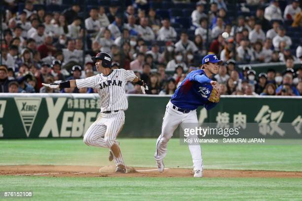 Infielder Shuta Tonosaki of Japan is forced out while Infielder Jung Hyun of South Korea throws to the first base to make a double play in the bottom...