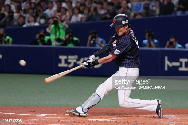 Infielder Sosuke Genda of Japan hits a threerun triple in the top of 2nd inning during the game six between Japan and MLB All Stars at Nagoya Dome on...