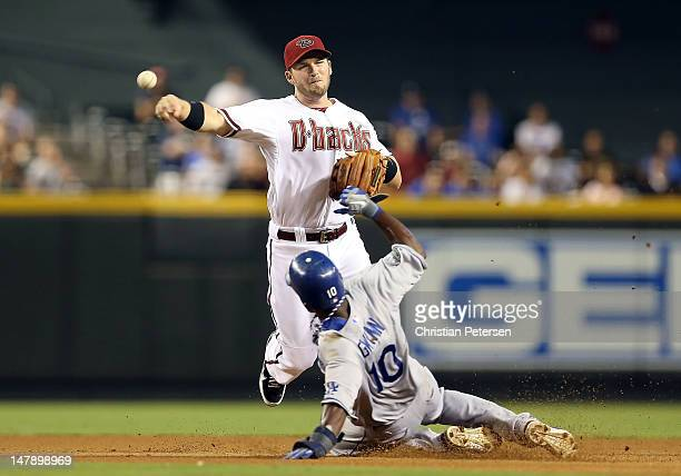 Infielder Stephen Drew of the Arizona Diamondbacks throws over the sliding Tony Gwynn of the Los Angeles Dodgers to compete a double play during the...