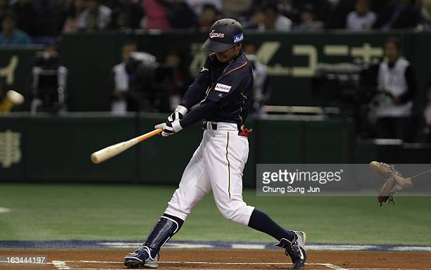 Infielder Takashi Toritani of Japan hits a solo home run top of the first inning during the World Baseball Classic Second Round Pool 1 game between...