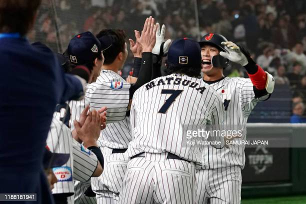 Infielder Tetsuto Yamada of Japan is congratulated by team mates after hitting a three-run homer to make it 3-4 in the bottom of 2nd inning during...