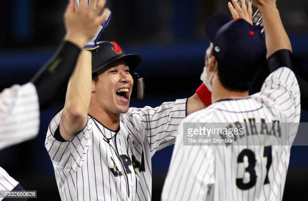 Infielder Tetsuto Yamada of Team Japan is congratulated by his team mate Ryoya Kurihara the eighth inning against Team Republic of Korea during the...