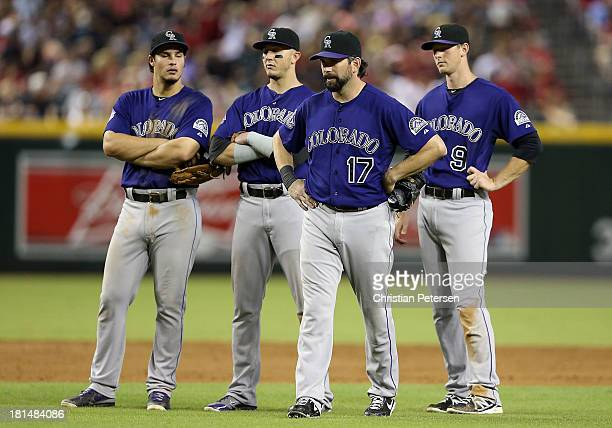 Infielder Todd Helton of the Colorado Rockies walks back to first base after standing with Nolan Arenado Troy Tulowitzki and Corey Dickerson during...