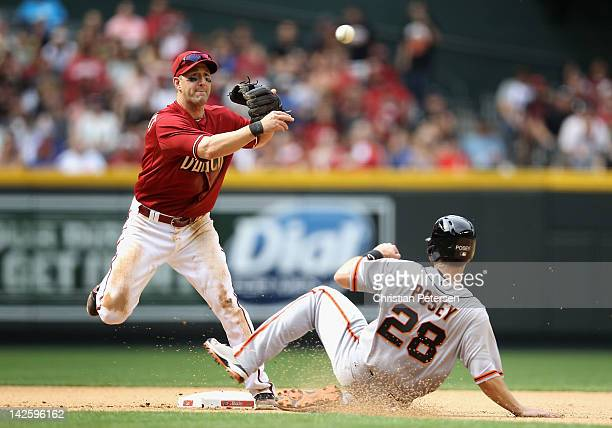 Infielder Willie Bloomquist of the Arizona Diamondbacks throws over the sliding Buster Posey of the San Francisco Giants to complete a double play...