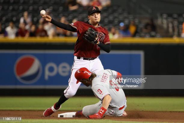 Infielder Wilmer Flores of the Arizona Diamondbacks throws over the sliding Bryce Harper of the Philadelphia Phillies as he attempts an unsuccessful...