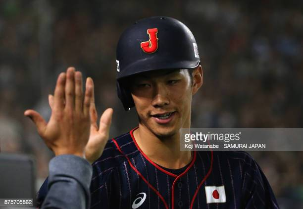 Infielder Yota Kyoda of Japan high fives after scoring a run by a walk in the top of seventh inning during the Eneos Asia Professional Baseball...