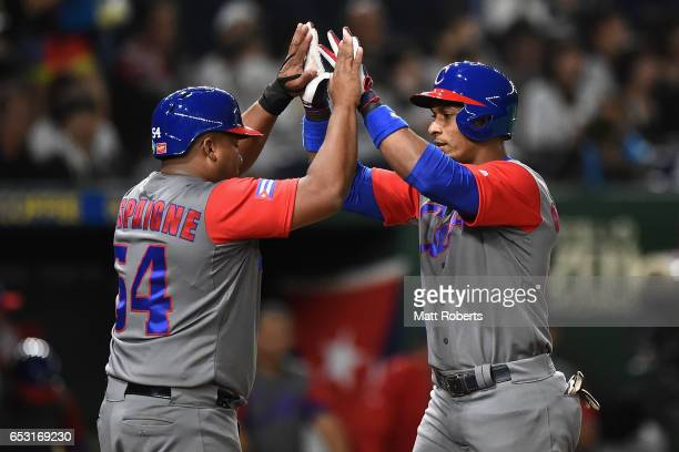 Infielder Yurisbel Gracial of Cuba high fives with Outfielder Alfredo Despaigne after hitting a two run homerun in the top of the second inning...