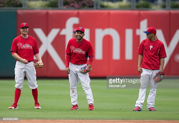 Infielders Cody Asche Andres Blanco and Cesar Hernandez of the Philadelphia Phillies warm up prior to a game against the Pittsburgh Pirates on...