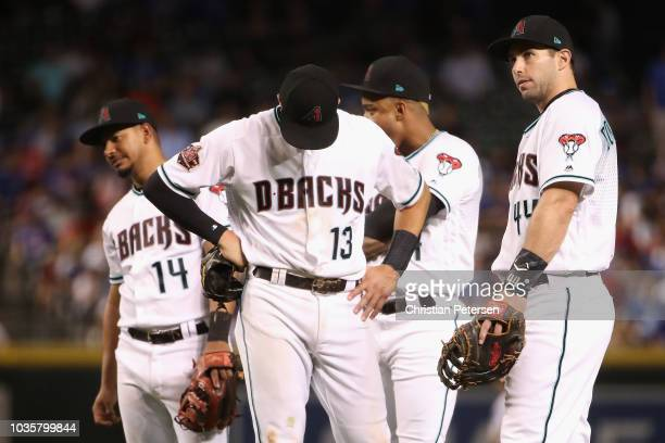 Infielders Eduardo Escobar Nick Ahmed Ketel Marte and Paul Goldschmidt of the Arizona Diamondbacks react on the field during a break from the fifth...