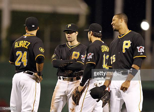 Infielders Pedro Alvarez Neil Walker Chase D'Arnaud and Derrek Lee of the Pittsburgh Pirates talk while a relief pitcher warms up against the Houston...