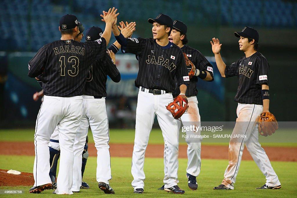 Infielders Sho Nakata #13, Hayato Sakamoto #6, Nobuhiro Matsuda #3, Tetsuto Yamada #23 high five after their team's win in the WBSC Premier 12 match between Japan and Dominican Republic at the Taoyuan International Baseball Stadium on November 12, 2015 in Taipei, Taiwan.