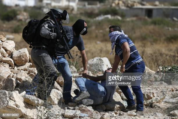 Infiltrated undercover members of the Israeli security forces detain a Palestinian protester during clashes near the Jewish settlement of Beit El on...