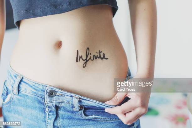 infinite tattoo word in a woman belly