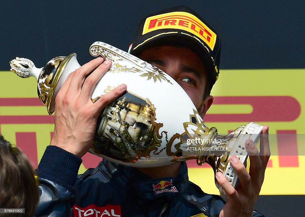 Infiniti Red Bull Racing's Australian driver Daniel Ricciardo kisses his trophy to celebrate his third place on the podium at the Hungaroring circuit in Budapest on July 24, 2016 after the Hungarian Formula One Grand Prix. / AFP / ATTILA