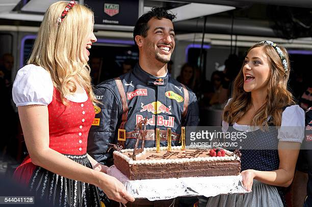 Infiniti Red Bull Racing's Australian driver Daniel Ricciardo poses with his 27th birthday cake in the pit lane before the first practice session of...
