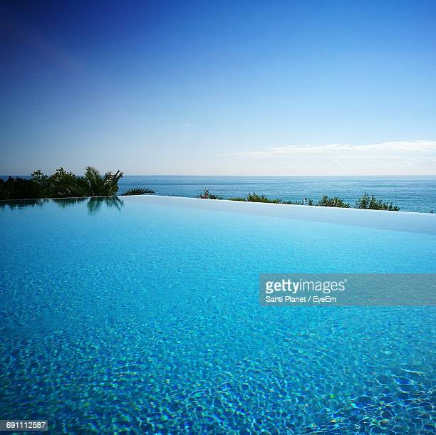 infinity pool and sea against blue sky - infinity pool foto e immagini stock