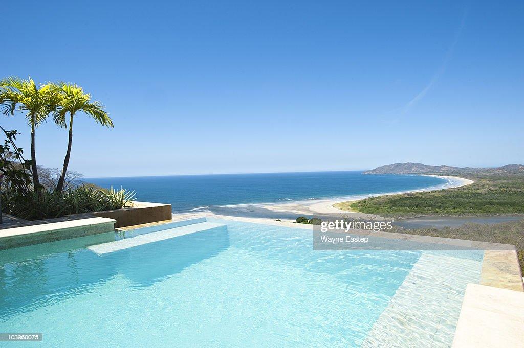 Infinity pool overlooking beach and Pacific Ocean : Foto de stock