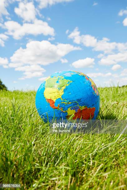 inflatable globe on a meadow against sky - one world stock pictures, royalty-free photos & images