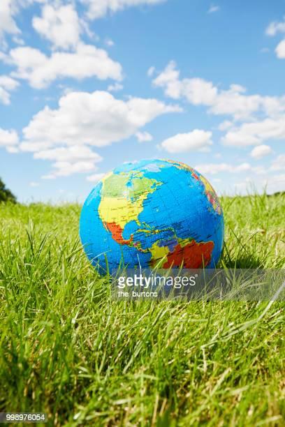 inflatable globe on a meadow against sky - objet vert photos et images de collection