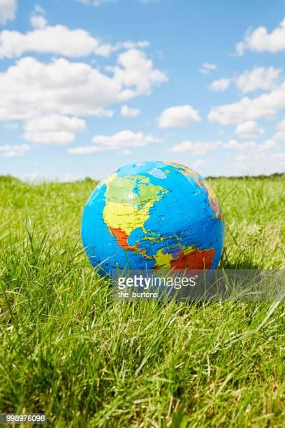 inflatable globe on a meadow against sky - blauer ball in hamburg stock-fotos und bilder
