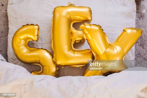 inflatable letters sex in bed - sex stock photos and pictures