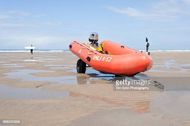 Inflatable orange lifeboat resting on a trailor on the beach