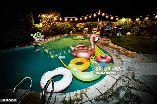 Inflatable pool toys in backyard pool during party on summer evening